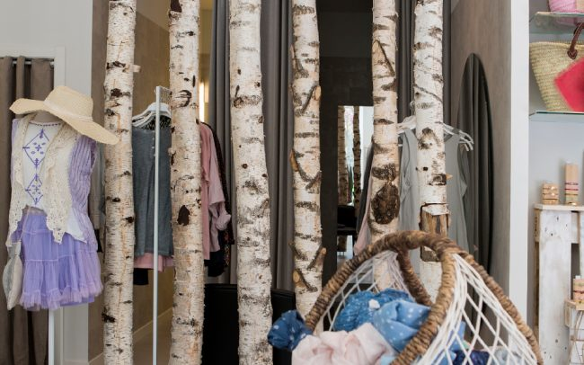 decoración tienda ropa moda con troncos árboles